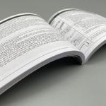 Aufgeschlagener Katalog mit Klebebindung.